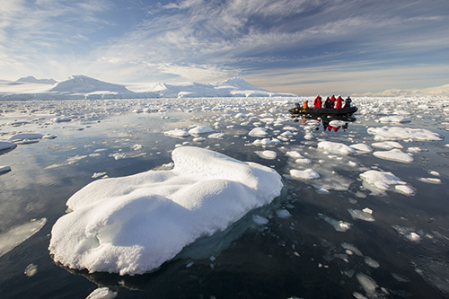 Members of an expedition cruise to Antarctica in a Zodiak in Fournier Bay in the Gerlache Strait on the Antarctic Peninsular.