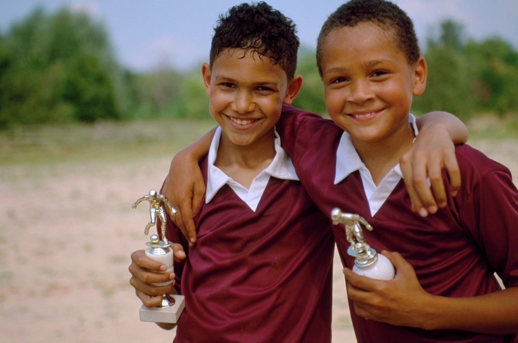 Two friends smiling with trophies