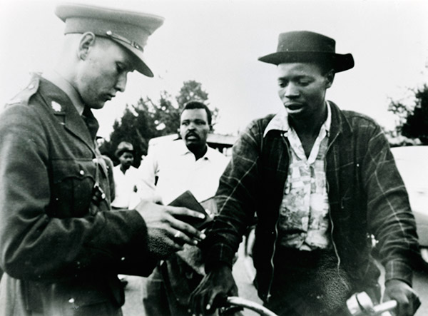Policeman inspecting papers during the Apartheid era. © Africa Media Online