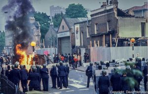 Brixton riots, London 1981. Police advance on barricades in Railton Road as they clear the streets.© David Hoffman